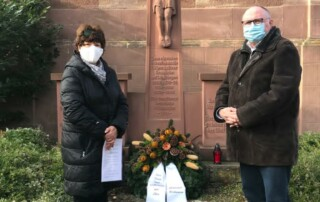 Bürgermeisterin Anne- Marie Kreis und Stellvertreter Dr. Mathias Diederich legten am Ehrenmal einen Kranz nieder und zündeten zum Gedenken Kerzen an. Foto: Gemeinde Bilshausen